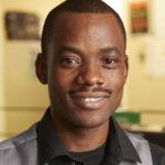 Young, black man smiles at camera